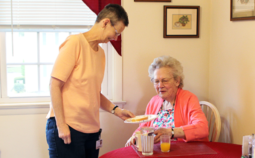 Woman serves Chapel Pointe resident breakfast in her apartment